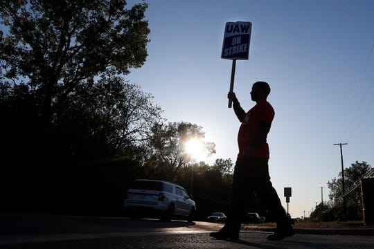 A member of the United Auto Workers walks the picket line at the General Motors Romulus Powertrain plant in Romulus.