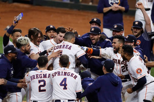Houston Astros shortstop Carlos Correa is mobbed by his teammates at home plate after hitting a walk-off home run off New York Yankees pitcher J.A. Happ during the 11th inning.