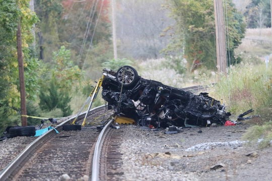 The remains of a Porsche SUV that plummeted off an overpass rests on train tracks below, where it burst into flames Sunday afternoon, killing two teenagers and sending a third to a hospital with serious injuries. in Pearl River, NY, Sunday, October 13, 2019.