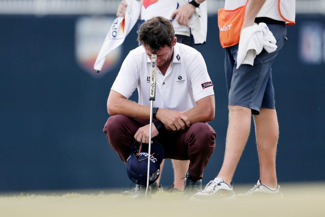Lanto Griffin cries as he squats and rests his head on his putter Sunday after winning the Houston Open golf tournament.