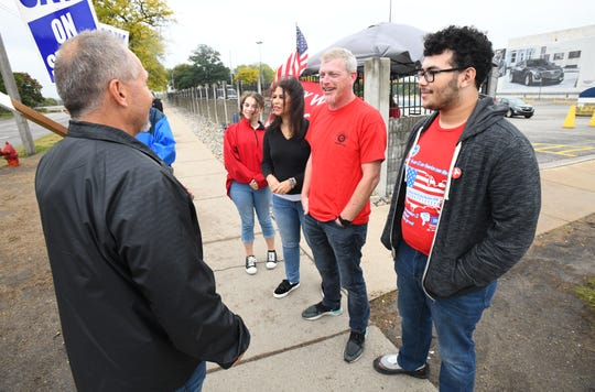 Matt Moorhead, center right, and his family, daughter Chelsea, 15, wife Alyson and son Spencer, 18, talks to a fellow UAW member on the picket line in front of the Grand River Assembly Plant in Lansing.
