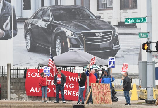 Matt Moorhead (in red shirt holding sign) takes his turn on the picket line  in front of the Grand River Assembly Plant in Lansing, while his wife Alyson takes a photo their daughter Chelsea, 15, left,  and son Spencer, 18.