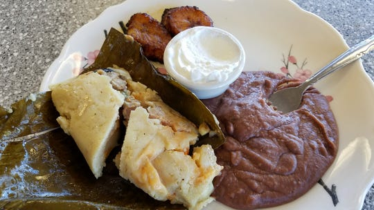 A Salvadoran banana-leaf tamal with refried beans, plantains and sour cream at Los Alfaro's.