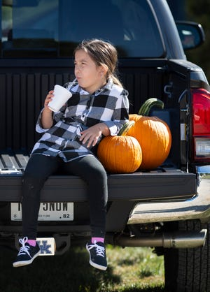 Natalie Allen, 8, of Evansville sips an apple cider slushy after a morning of pumpkin picking at Goebel Farms in Evansville Monday. Natalie and her family, including 11-day-old Noelle and mom and dad, Allison and Eric Allen, were all along for the trip, but Noelle failed to wake up even once during the adventure. With fall weather beckoning, visit courierpress.com for a list of area corn mazes, pumpkin patches and more.