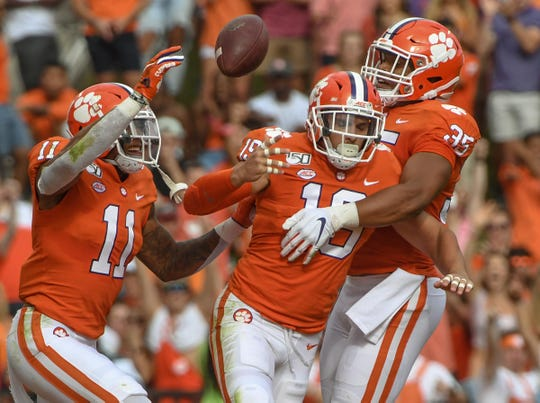 Clemson defensive back Tanner Muse (19), middle, flips the football to a referee after intercepting the ball, then celebrating with teammates safety Isaiah Simmons (11) and linebacker Justin Foster (35) during the first quarter at Memorial Stadium in Clemson, South Carolina Saturday, October 12, 2019.