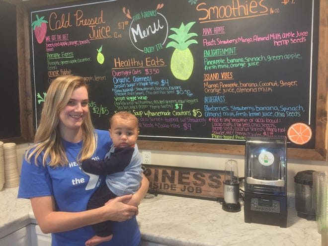 Henderson Juice Co. owner Emily Hunter poses with her youngest child, Devin, in front of the menu board.