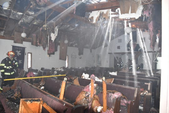 Indianapolis firefighters work inside Bethany Rembrandt Church after a fire caused serious damage to the structure.