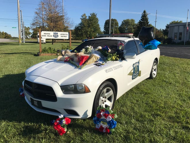Stuffed animals, flowers and balloons decorate an Indiana State Police patrol car outside of ISP's post as a way for the public to remember Trooper Peter Stephan, who died Friday night.