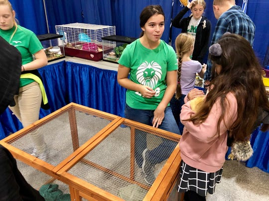 Lafayette Middle School students in the Environmental Sciences Academy let visitors hold animals they have on display, including ferrets, guinea pigs and iguanas during Magnet Academies Showcase Saturday, Oct. 12.
