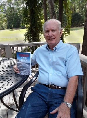 """Lancaster native and mystery author Steve McMillen poses with his latest novel, """"Terror Grips the Beach."""""""