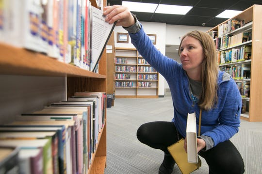 Fowlerville resident Aimee Rinehart selects books at the Fowlerville District Library Monday, Oct. 14, 2019.