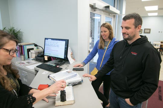 Fowlerville District Library circulation aide Mary Hudson checks out books for patrons Aimee and Tim Rinehart Monday, Oct. 14, 2019.
