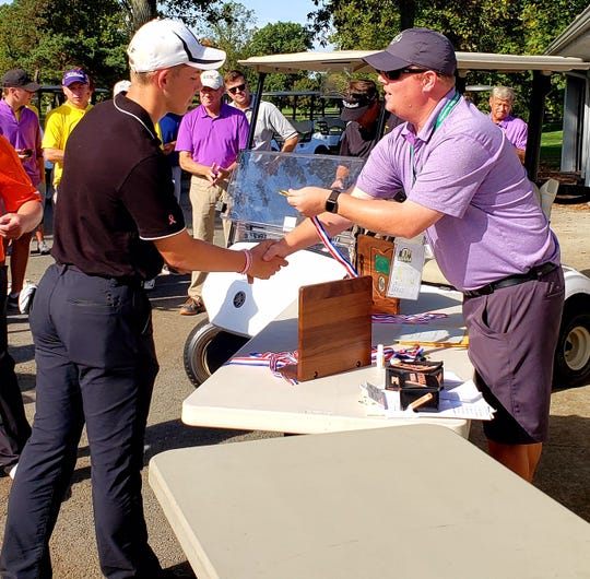 Ashland sophomore Tyler Sabo receives his medal as co-medalist at the Division I district golf tournament.