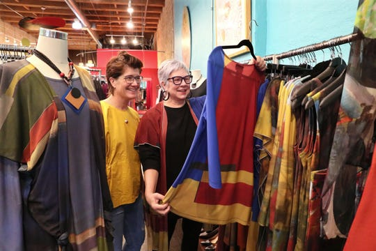 Artist Pamela Anderson, right, and Carrie Arrouet of Lela Boutique look over clothing based on Anderson's paintings.