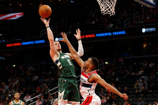 Bucks guard Donte DiVincenzo puts up a shot down low over Wizards guard Phil Booth in the fourth quarter.