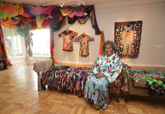 Artist Rosemary Ollison wears clothing she designed and created. That's her work on the wall, too, at the Lynden Sculpture Garden studio in River Hills.