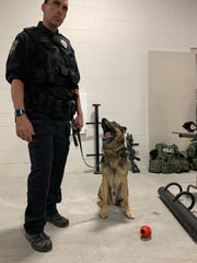 K9 cop Sirius keeps on eye on his handler, Officer Shawn Diedrich, at the tail-end of an open house showing off the Muskego Police Department's new station on Oct. 10. Diedrich explained Sirius' strategic importance to tour group members.