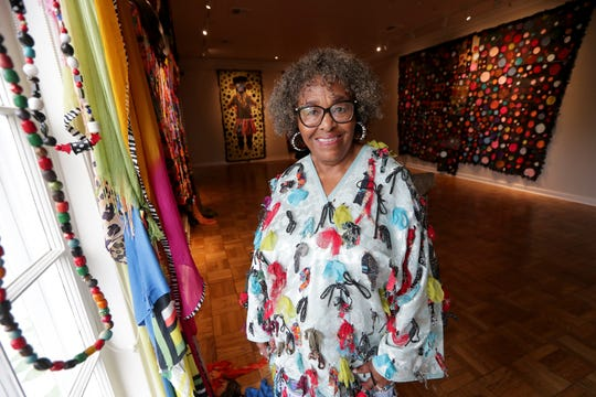 Rosemary Ollison wears clothing she designed and created at the Lynden Sculpture Garden studio in River Hills. That's her artwork on the wall, too.
