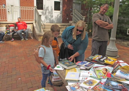 Kristin Harbulak helps her 6-year-old daughter, Cadence, and 8-year-old son, Camden, pick out books at a free book exchange at Teddy Bear Park in Stillwater. The family also dropped off half a dozen books during the event.
