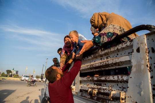 Syrians fleeing the Turkish advance arrive at the town of Tal Tamr in north Syria on Monday, Oct. 14, 2019. Syrian government troops moved into towns and villages in northern Syria on Monday, setting up a potential clash with Turkish-led forces advancing in the area as long-standing alliances in the region begin to shift or crumble following the pullback of U.S. forces.