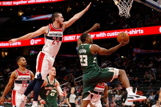 Bucks guard Sterling Brown goes in for a reverse layup against Wizards guard Garrison Mathews during the fourth quarter.