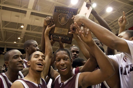 St. Jude players hold up the trophy and celebrate their 64-58 win over Brantley in the AHSAA 1A Southeast Regional Tournament Championship at Troy University Friday afternoon, Feb. 24, 2006. (Garrett Davis, Montgomery Advertiser)
