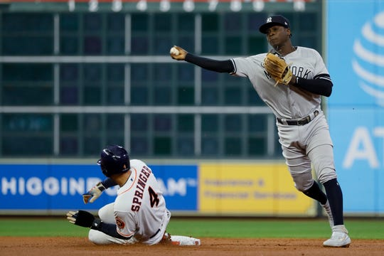 Houston Astros' George Springer is forced out at second by New York Yankees shortstop Didi Gregorius after Michael Brantley hit into a double play during the first inning in Game 2 of baseball's American League Championship Series Sunday, Oct. 13, 2019, in Houston. (AP Photo/Matt Slocum)