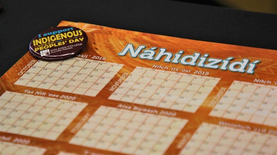 A free calendar in the Navajo language and a button advertising San Juan College's Indigenous Peoples Day celebration sits on a table at San Juan College on Oct. 14 2019.
