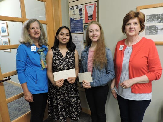 Friends of Northville District Library President Martha Nork (right) and Friends Board Member Linda Schwelnus (left) present scholarships to two Northville graduating seniors who volunteered their time at the library, Shruti Pandey (second from left) and Gabriela Iriarte (second from right).
