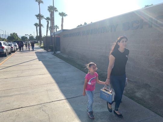 A mother and daughter walk to James Madison Elementary School on Monday, Oct. 14, 2019, where a meeting was called to discuss the health and safety issues there and plans to relocate students to another facility.