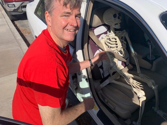 Fourth-grade teacher Brian Schreiber retrieved vital teaching tools from James Madison Elementary School on Monday Oct. 14, 2019, such as his skeleton, Mr. Freddy, seen here having his seat belt buckled. He had to sign a waiver to get in his classroom.