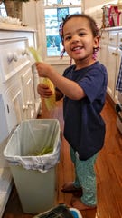 Sarah Isaacson, age 3, loves to shuck corn for dinner