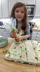 Grace Isaacson decorates her 7th birthday cake with a butterfly flower garden design.