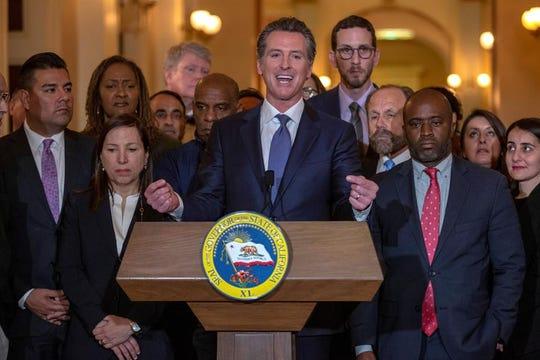 El gobernador de California, el demócrata Gavin Newsom (c), ofrece una rueda de prensa en Sacramento.