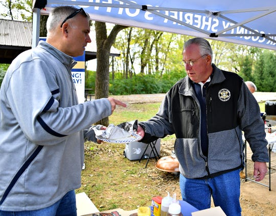 Sheriff Richard Keuerleber, right, of the York County Sheriff's Department, serve a Mac & Cheese Dog to Spring Garden Township Police Chief George Swartz as York County law enforcement agencies compete with their best hot dog recipes during the second annual Top Dog Contest and Fundraiser at John C. Rudy Park in Springettsbury Township, Sunday, Oct. 13, 2019. Dawn J. Sagert photo