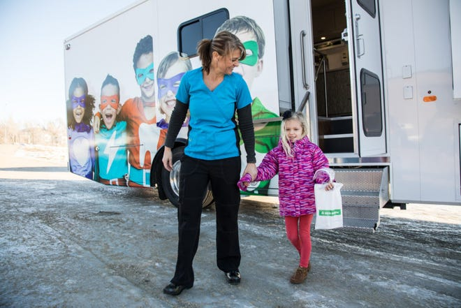 A young girl and a dental assistant walk away after receiving treatment at one of two mobile dental health clinics operated by Delta Dental of South Dakota. The mobile clinics have provided about $21 million worth of subsidized dental care to roughly 40,000 patients in more than 80 communities over the past 15 years.