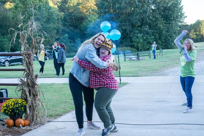 Camper Ronni Braun is welcomed to Camp Barnabas this past weekend with a hug from staffer Sarah Nelson. In the background, staffer Lizzie Lalonde announced Braun's arrival.