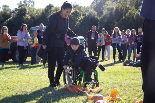 Camper Chance Presely bashes a pumpkin with a bat at Camp Barnabas this past weekend.
