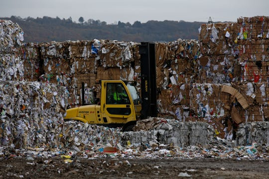 A forklift truck driver moves bales of recycled cardboard at a paper mill in the U.K.