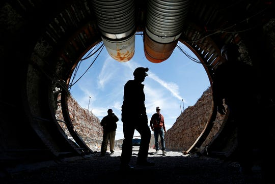 FILE - In this April 9, 2015, file photo, people walk into the south portal of Yucca Mountain during a congressional tour of the proposed radioactive waste dump near Mercury, Nev., 90 miles northwest of Las Vegas. A fight is raging in courts and Congress over where radioactive materials should be stored and how to safely get the dangerous remnants of decades of bomb-making and power generation to a permanent resting place. (AP Photo/John Locher, File)