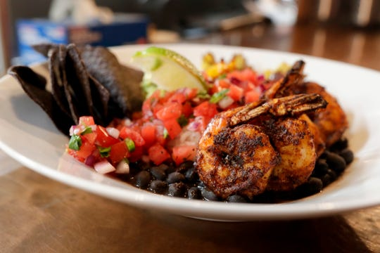 "The menu at Jeri's Midtown Cafe includes the ""Righteous Rice Bowl,"" which includes steamed Jasmine rice, seasoned black beans, fresh pico de gallo, handmade guacamole, a lime wedge, and blue corn chips, served here with jumbo shrimp."