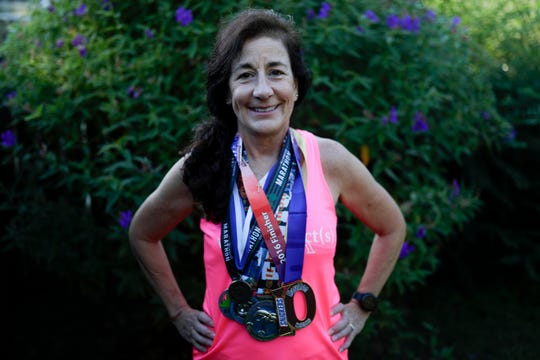 Debbie Peters, a breast cancer survivor and runner, poses with some of her most prized medals she received from finishing marathons Thursday, Oct. 10, 2019.