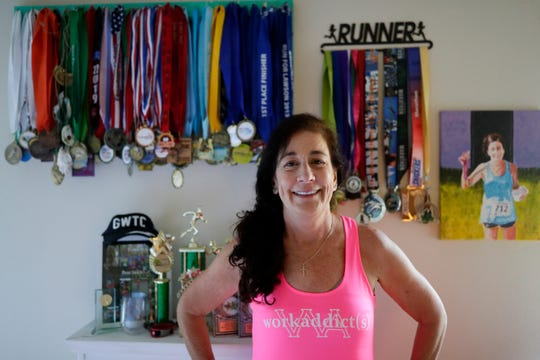 Debbie Peters, a breast cancer survivor and runner, poses with her medals she keeps on display in her bedroom Thursday, Oct. 10, 2019.