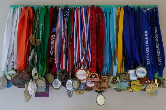 Debbie Peters, a breast cancer survivor and runner, keeps a multitude of medals on display in her bedroom.