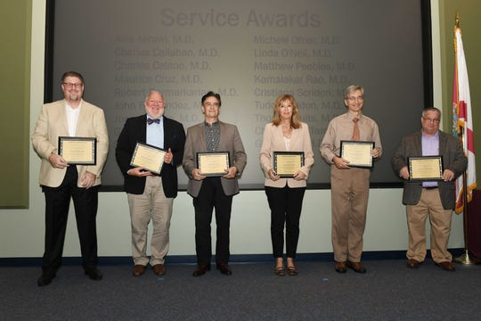 Ten-year service award winners, from left, Dr. Matthew Peebles, Dr. Robert Dermarkarian, Dr. Maurice Cruz, Dr. Cristiana Scridon, Dr. Tudor Scridon and Dr. Charles Callahan at the Fort Pierce Regional Campus of Florida State University College of Medicine.