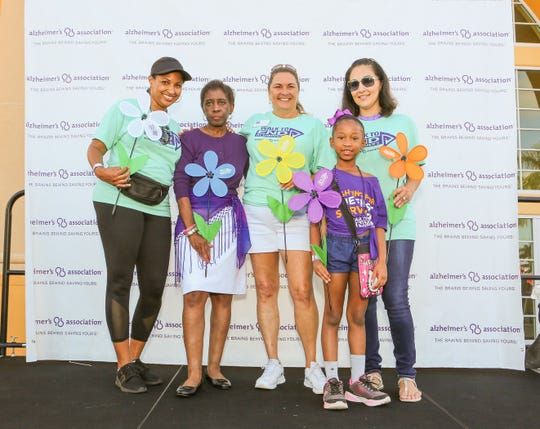 Walk to End Alzheimer's participants Roshini Lakram, left, Cecilia Norwood, Dorothy Duve, Amari Lawrence and Christine Rigg at the Port St. Lucie Civic Center on Sept. 28, 2019. The flowers they're holding symbolize the connection to the disease: Blue for someone who is living with a diagnosis; yellow for a caregiver of someone with the disease; orange for an advocate/supporter, and purple for someone who has lost a loved one to the disease. The white flower represents the hope for Alzheimer's first survivor.
