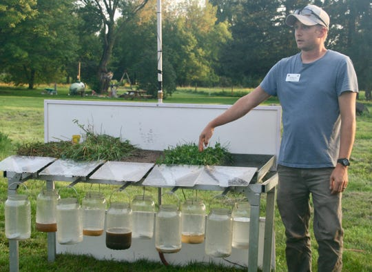 Using an NRCS rainfall simulator to demonstrate the effect of rainfall on different cropping systems, the runoff container below the conventionally planted field sample, third from left, produced the most runoff while soils from woodland, pasture and a former grass barnyard had minimal runoff.