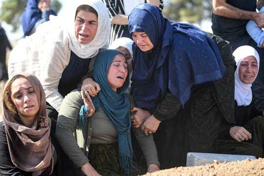 Relatives mourn in front of the grave of Halil Yagmur who was killed in a mortar attack a day earlier in Suruc near northern Syria border, during funeral ceremony in Suruc on October 12, 2019.