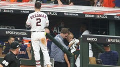 A security guard is tended to in the Astros dugout after being hit by a foul ball.
