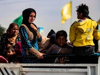 Displaced Syrians sit in the back of a pick up truck as Arab and Kurdish civilians flee amid Turkey's military assault on Kurdish-controlled areas in northeastern Syria, on October 11, 2019 in the town of Tal Tamr in the countryside of Syria's northeastern Hasakeh province.